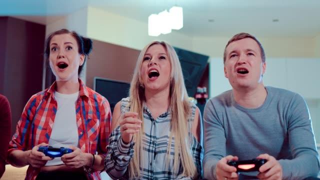 Grupo-de-amigos-que-juegan-video-juegos-en-piso-moderno