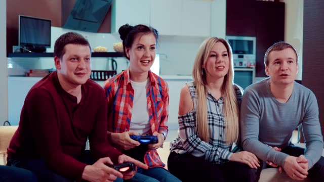 Parejas-felices-en-amor-personas-relajarse-jugando-videojuegos-con-controladores-inalámbricos-y-diversión-interior-en-piso-moderno