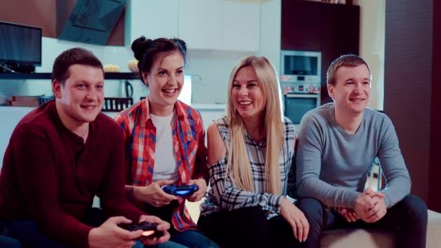 Feliz-grupo-de-amigos-masculinos-y-femeninos-jugando-videojuegos-con-controladores-inalámbricos-de-risa