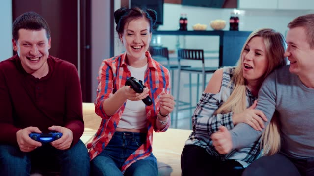 Happy-company-of-the-friends-enjoy-relaxing-by-playing-videogames-and-having-fun-indoor-in-modern-flat