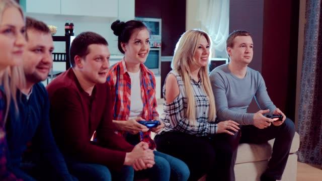 Compañía-de-los-amigos-de-relajarse-en-el-sofá-jugando-videojuegos-y-divirtiéndose-en-piso-moderno