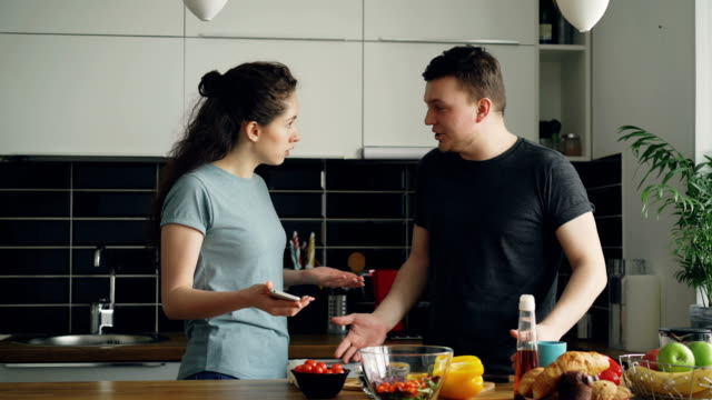 young-curly-woman-showing-something-unpleasant-in-husband-s-phone-while-he-is-cooking-they-are-shouting-and-quarrelling-man-is-angry-and-irritated
