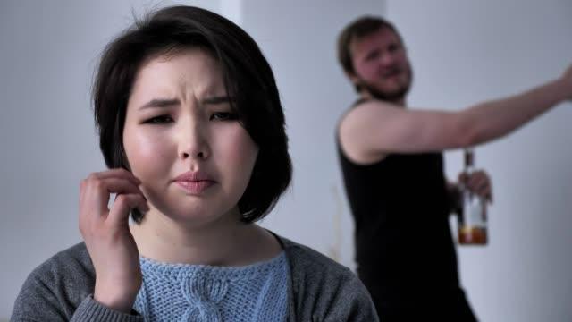 Retrato-de-una-chica-triste-deprimida-marido-borracho-en-el-fondo-Jura-pelea-conflicto-mira-a-la-cámara-50-fps