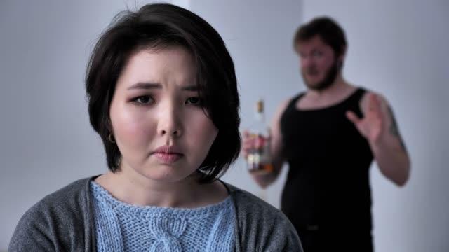 Porträt-einer-traurig-deprimiert-Asiatin-betrunken-Mann-im-Hintergrund-schwört-Alkohol-Konflikte-in-die-Kamera-schaut-50-fps