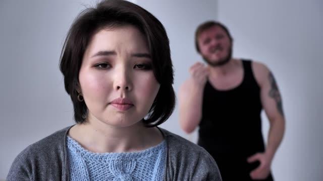 Retrato-de-una-chica-triste-deprimida-marido-borracho-en-el-fondo-es-afligido-alcohol-violencia-mira-a-la-cámara-60-fps