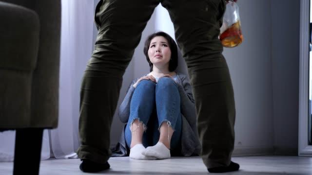 Triste-mujer-asiática-se-sienta-en-el-suelo-ebrio-marido-preparando-para-golpear-a-su-esposa-un-conflicto-en-la-familia-violencia-50-fps