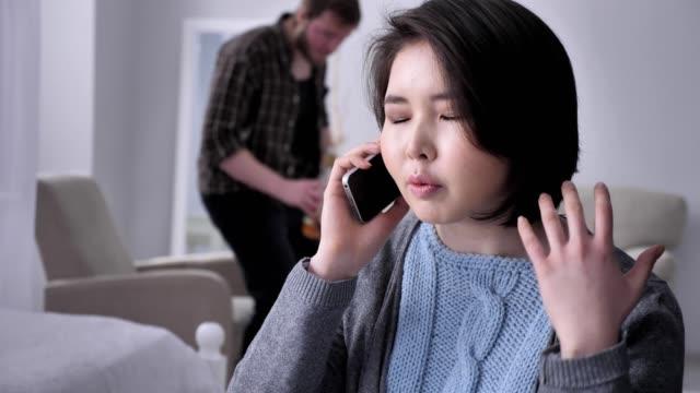 Junge-traurig-Asiatin-besorgt-das-Telefonieren-mittels-Smartphone-Smartphone-Porträt-betrunken-Mann-im-Hintergrund-50-fps