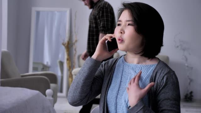 Junge-traurig-Asiatin-spricht-aggressiv-auf-dem-Handy-mit-Smartphone-Portrait-betrunken-Mann-im-Hintergrund-50-fps
