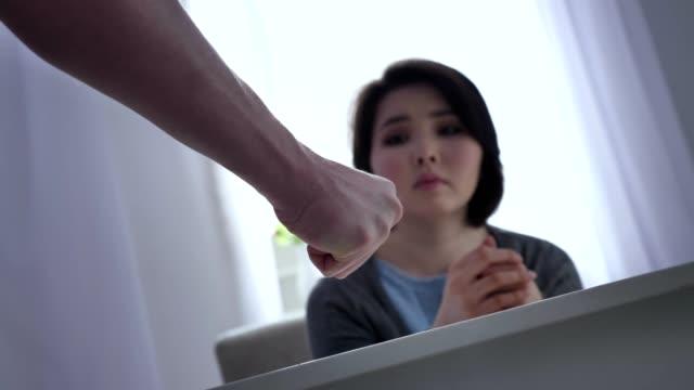 Konzept-von-häuslicher-Gewalt-in-der-Familie-männliche-Faust-Angst-asiatische-Frau-sitzt-am-Tisch-im-Hintergrund-50-fps