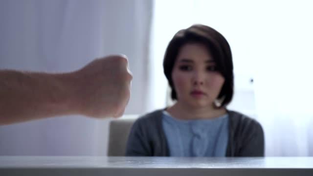 Konzept-von-häuslicher-Gewalt-in-der-Familie-schlägt-Faust-auf-Tisch-ängstlich-asiatische-Frau-sitzt-am-Tisch-im-Hintergrund-50-fps