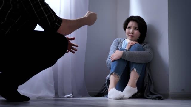 Triste-mujer-asiática-sienta-en-el-piso-enojado-marido-amenaza-conflicto-en-la-familia-violencia-50-fps
