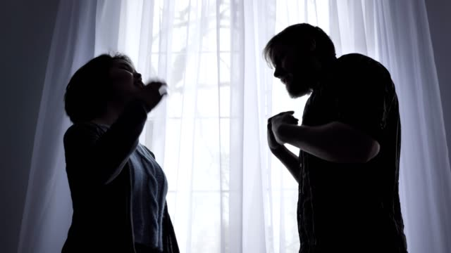Der-Streit-einer-jungen-Familie-der-Mann-schreit-an-seine-Frau-die-Konflikt-Konzept-häusliche-Gewalt-ein-Fenster-im-Hintergrund-50-fps