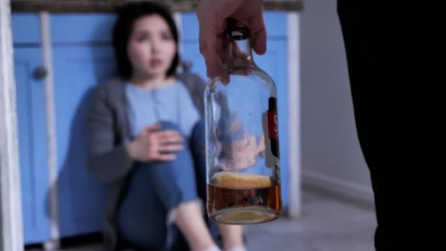 Triste-solitaria-asiático-joven-sentado-en-el-suelo-en-la-cocina-sosteniendo-sus-rodillas-con-los-brazos-concepto-de-violencia-doméstica-marido-borracho-va-a-vencer-a-su-esposa-50-fps