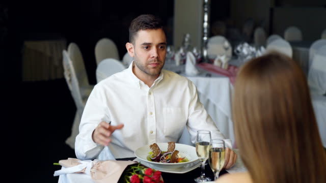 Young-couple-is-quarreling-while-dining-in-restaurant-shouting-and-gesturing-Bouquet-of-roses-sparking-champagne-glasses-and-plates-with-food-are-visible-