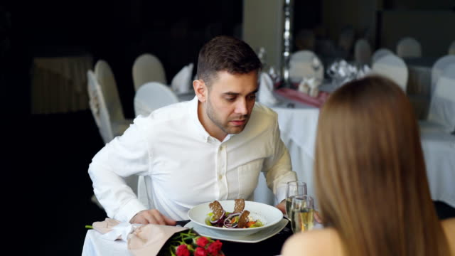 Young-bearded-man-is-arguing-with-his-girlfriend-while-dining-in-restaurant-then-leaving-Lovers-quarrel-negative-emotions-and-relationship-crisis-concept-