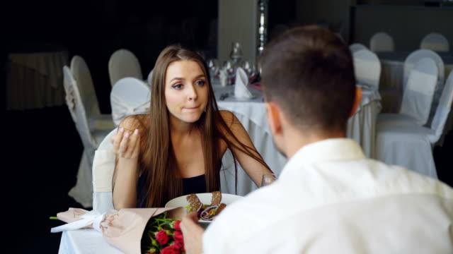 Señora-joven-enojada-está-discutiendo-con-su-novio-mientras-cenan-en-el-restaurante-entonces-dejando-Los-amantes-de-la-pelea-las-emociones-negativas-y-concepto-de-crisis-de-relación-