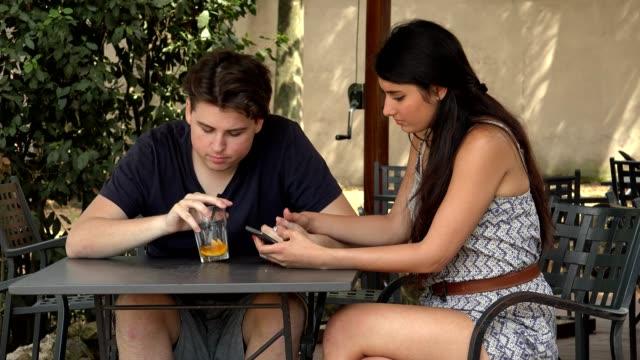 joven-pareja-discutiendo-sentados-en-el-bar-al-aire-libre