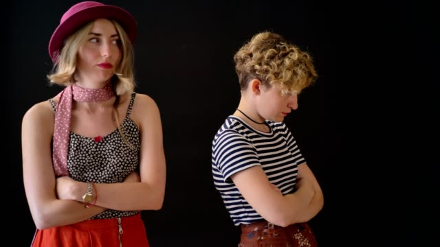 Two-young-charming-female-friends-have-conflict-offended-women-standing-with-crossed-hands-isolated-on-black-background