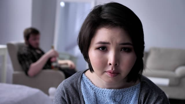 Portrait-of-a-sad-depressed-Asian-girl-drunk-husband-in-the-background-looking-at-the-camera-50-fps