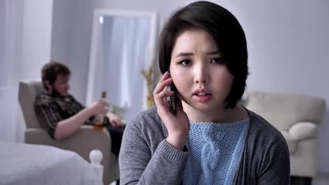 Young-sad-Asian-girl-anxiously-dials-a-number-calls-by-smartphone-portrait-looks-at-camera-drunk-husband-in-the-background-50-fps