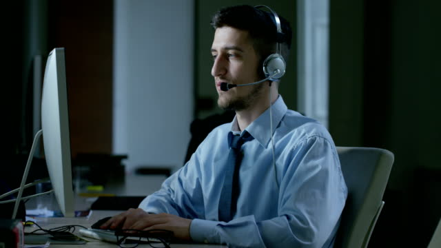 A-young-man-who-work-in-customer-service-or-in-some-airport-control-tower-station-answers-calls-to-phone-customers-with-a-smile-day-and-night-