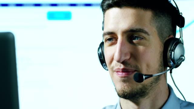 Un-hombre-joven-que-trabaja-en-servicio-al-cliente-o-en-alguna-estación-de-torre-de-control-del-aeropuerto-responde-a-las-llamadas-a-los-clientes-de-teléfono-con-una-sonrisa-día-y-noche-