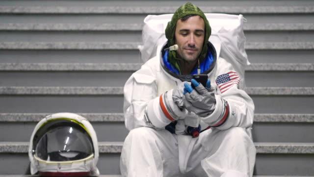 Un-hombre-vestido-de-astronauta-utiliza-el-smartphone-para-llamar-y-enviar-mensajes-Las-sonrisas-de-astronauta-mirando-el-teléfono-en-la-mano-