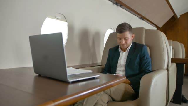 Businessman-chat-and-sit-in-armchair-in-private-jet