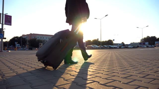 Tiro-de-irreconocible-hombre-caminando-en-la-calle-de-la-ciudad-y-tirando-de-maleta-sobre-ruedas-en-el-ocaso-de-la-grúa-Joven-hombre-de-negocios-mirando-su-reloj-y-va-con-el-equipaje-a-la-terminal-del-aeropuerto-Cerrar-vista-posterior
