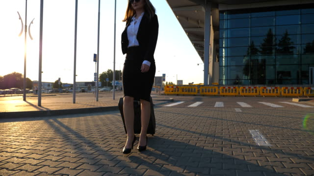 Mujer-joven-caminando-cerca-de-aparcamiento-en-el-aeropuerto-con-su-equipaje-en-el-atardecer-Piernas-femeninas-en-tacones-caminar-en-la-acera-Mujer-de-negocios-que-va-con-su-maleta-en-la-calle-urbanita-Lenta-de-cerca