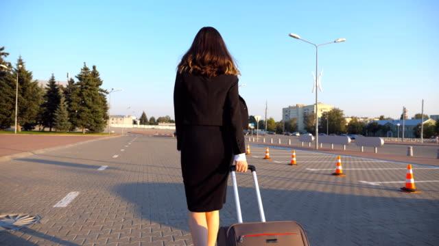 Mujer-de-negocios-con-su-maleta-va-desde-el-aeropuerto-al-estacionamiento-de-taxis-Mujer-caminando-con-su-equipaje-a-lo-largo-de-la-calle-de-la-ciudad-Piernas-femeninas-en-tacones-caminar-en-la-acera-Vista-trasera-del-nuevo-movimiento-lento