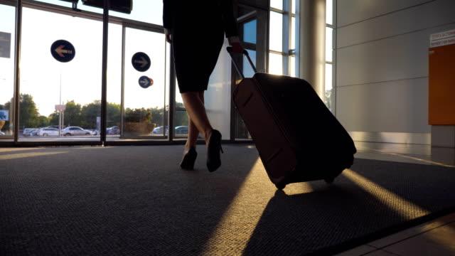 Señora-de-negocios-va-desde-el-aeropuerto-con-su-equipaje-Mujer-en-tacones-caminando-con-su-maleta-de-la-terminal-a-la-calle-de-la-ciudad-Chica-caminando-y-bolso-de-balanceo-en-las-ruedas-Concepto-de-viaje-Lenta-de-cerca
