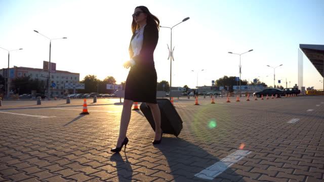 Mujer-en-calzado-tacón-alto-caminando-cerca-de-aparcamiento-en-el-aeropuerto-con-su-equipaje-en-el-atardecer-Empresaria-con-su-maleta-a-lo-largo-de-la-calle-de-la-ciudad-El-sol-de-la-llamarada-en-el-fondo-Lenta-de-cerca