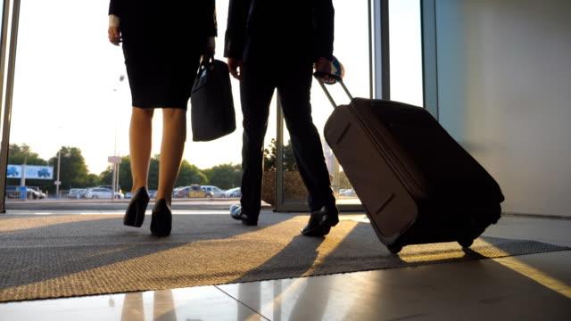 Hombre-de-negocios-y-de-la-mujer-con-el-equipaje-que-va-desde-el-aeropuerto-a-la-calle-de-la-ciudad-Siga-a-joven-empresario-llevar-maleta-sobre-ruedas-y-a-pie-con-su-colega-de-pasillo-de-la-terminal-Vista-posterior-de-cerca