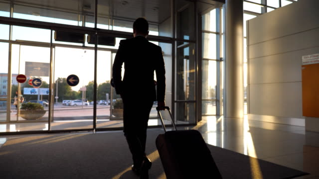 Unrecognizable-man-walking-through-glass-automatic-door-of-modern-airport-to-city-street-and-pulling-suitcase-on-wheels-Businessman-going-from-terminal-to-cars-parking-with-his-luggage-Rear-view