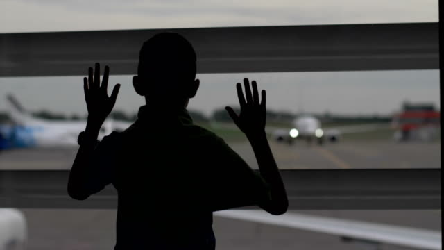 boy-stands-near-the-window-at-the-airport-and-looks-at-the-planes-the-boy-dreams-of-becoming-a-pilot