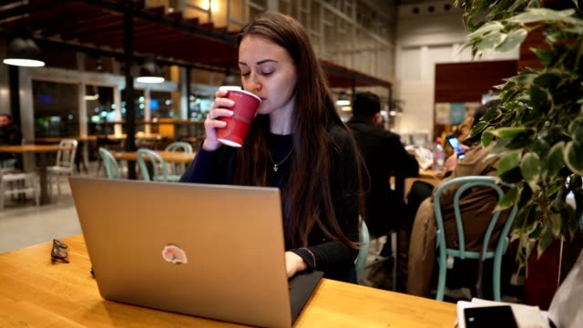 Young-beautiful-girl-working-with-laptop-and-drinking-coffee-at-a-wooden-table