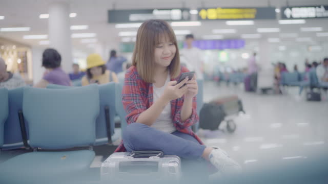 Happy-Asian-woman-using-and-checking-her-smartphone-while-sitting-on-chair-in-terminal-hall-while-waiting-her-flight-at-the-departure-gate-in-international-airport-Women-happy-in-airport-concept-