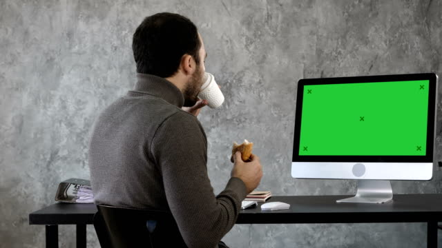 Business-man-in-the-office-having-breakfast-lunch-and-watching-something-on-the-mac-computer-Green-Screen-Mock-up-Display