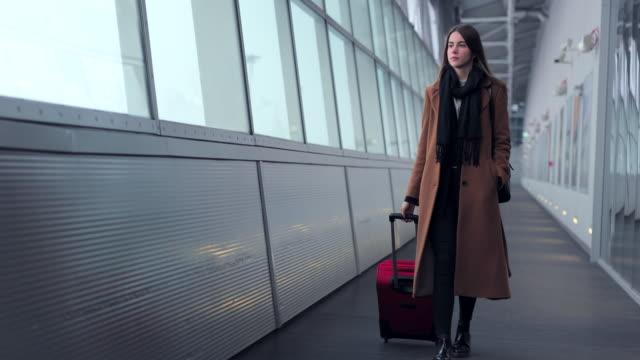 Geschäftsfrau-am-Flughafen-sprechen-auf-dem-Smartphone-während-des-Gehens-mit-Handgepäck-im-Bahnhof-oder-Airpot-zum-Flugsteig-gehen-Mädchen-mit-Handy-für-Unterhaltung-