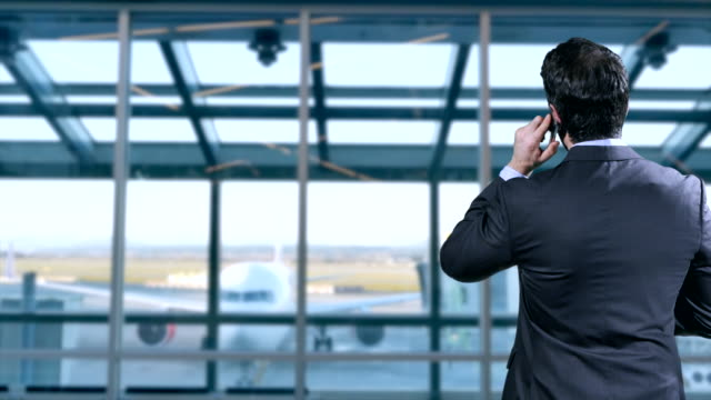 Man-in-Suit-talks-on-Mobile-Phone-as-Airplane-Taxis-towards-Terminal-Gate