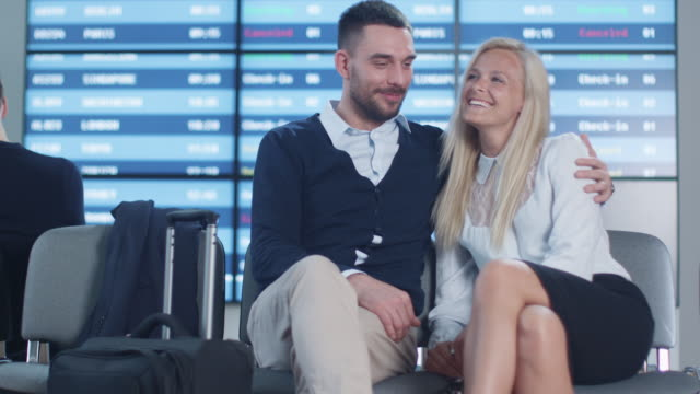 Man-and-Woman-Talking-while-Waiting-Boarding-at-Departure-Lounge-at-the-Airport-