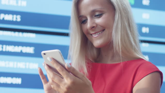 Attractive-Smiling-Blonde-Woman-Using-Mobile-Phone-next-to-Information-Board-in-the-Airport-
