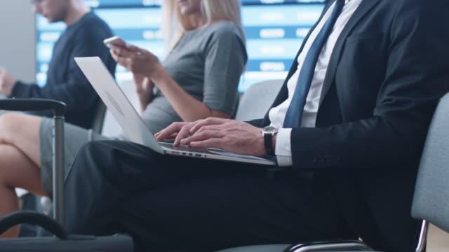 Hombre-de-negocios-trabajando-en-ordenador-portátil-mientras-espera-el-embarque-en-la-sala-de-embarque-en-el-aeropuerto-