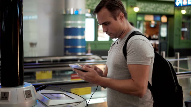 Handsome-young-man-in-airport-terminal-Standing-near-charging-stand-pluging-in-smartphone