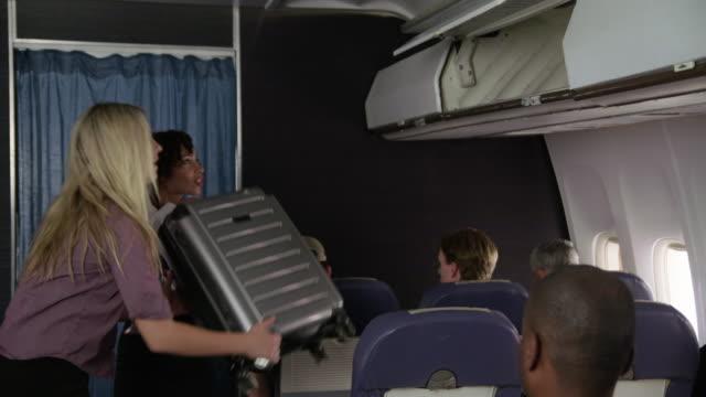 Flight-Attendant-Passagiere-mit-Gepäck-zu-helfen