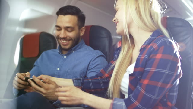 Beautiful-Young-Blonde-with-Handsome-Hispanic-Male-Play-with-Smartphone-on-their-Holiday-Flight-New-Commercial-Plane-Interior-is-Visible-