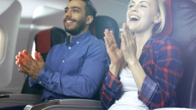 On-Board-of-Commercial-Airplane-Beautiful-Young-Blonde-and-Handsome-Hispanic-Male-Applauding-Pilot-s-Successful-Landing-Aerplane-s-Interior-is-Visible-Sun-Shines-Through-Window-