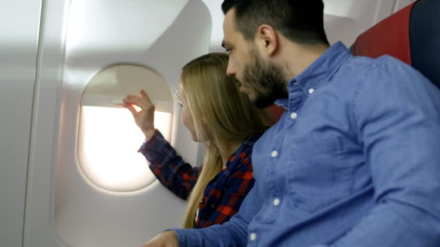 On-a-Commercial-Plane-Flight-Beautiful-Blonde-Passenger-Opens-Window-Shade-and-Wakes-Her-Sleeping-Hispanic-Male-Neighbor-New-Airplane-has-Beautifully-Designed-Interior-