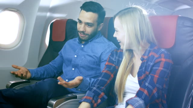 On-a-Commercial-Plane-Flight-Handsome-Hispanic-Man-Tells-Funny-Story-to-His-Beautiful-Blonde-Girlfriend-Both-Laugh-They-Travel-in-New-Airplane-with-Sun-Shining-Through-the-Window-